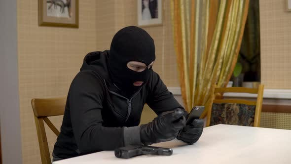 Thumbnail for A Robber Is Trying To Hack Into a Phone, A Masked Thug Is Sitting in a House and Cannot Hack