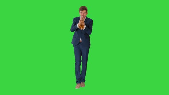Thumbnail for Young Man in Suit Playing a Trumpet While Walking on a Green Screen, Chroma Key.