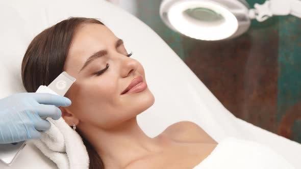 Schöne Frau, die Gesichtsbehandlung mit Kosmetologie-APPARAT erhält
