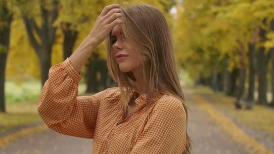 Cover Image for Profile Portrait of a Confident Caucasian Woman Standing on the Road in the Autumn Park