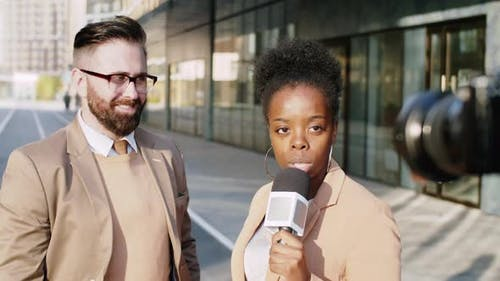 Businessman Giving Interview to Black Female Journalist Outdoors