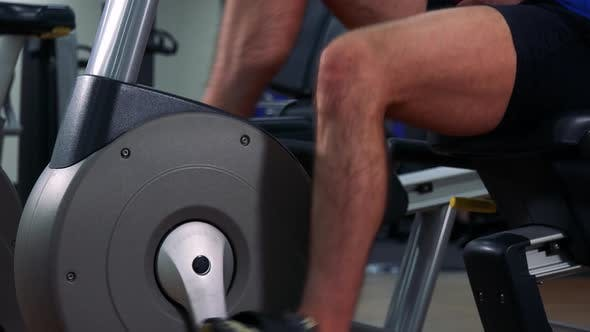 Thumbnail for A Fit Man Trains on a Recumbent Bike in a Gym - Closeup on Legs