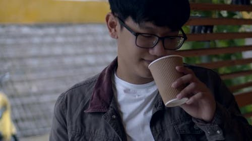 Man Asian in Glasses a Teenager Drinks Coffee.