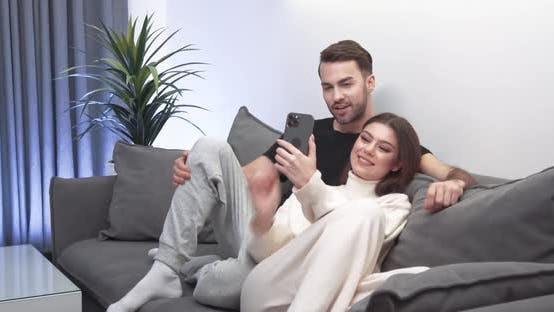 Young Couple Takes a Selfie on a Smartphone a Guy and a Girl Sit on the Sofa in the Living Room and