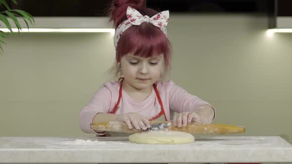 Cover Image for Cooking Pizza. Little Child in Apron Sprinkle the Dough with Flour in Kitchen