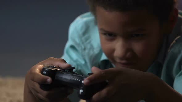 Thumbnail for Mixed-Race Boy Lying on Floor with Play Station Control and Playing Video Games