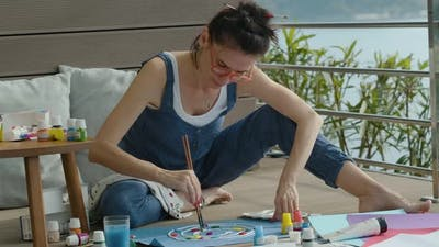 Young Woman Sitting on Terrace Floor and Painting Drawing on Paper with Acrylic Paint Rbbro