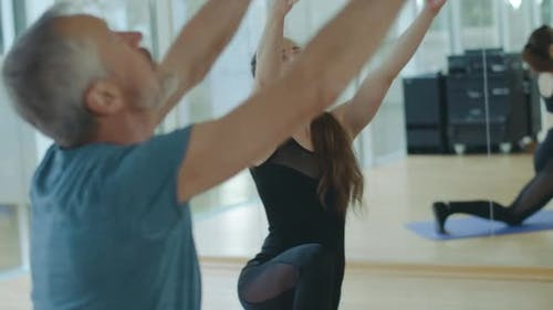 Live Camera Follow Movement of Caucasian Mid-adult Man and Young Woman Doing Breathing Exercise