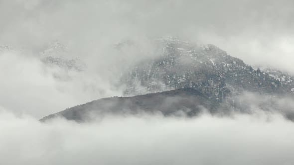 Clouds surrounding mountains in time lapse
