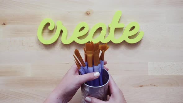 Thumbnail for Green create sign with paint brushes on the table.