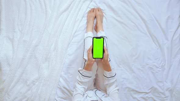 Thumbnail for Above View Woman Using Mobile Sits in Bedroom