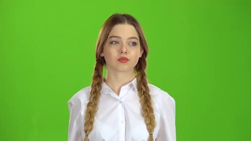 Student in a White Blouse and Pigtails Shows a Fis. Green Screen