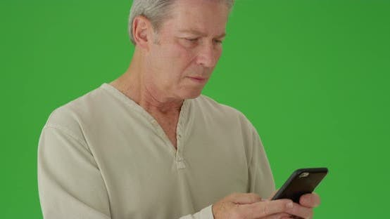 Thumbnail for Portrait of a mature white man texting in front of green screen