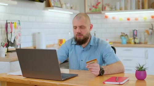 Attractive Bearded Hipster Paying Bills Online with Credit Card and Laptop