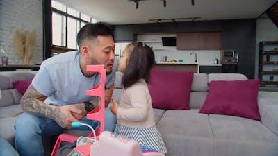Caring Asian Dad Babysitting Toddler Daughter at Home