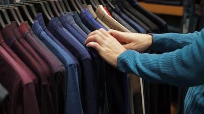 Man Choosing Shirt at Clothing Store