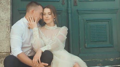 Romantic wedding couple sitting against green door in old town in Montenegro.