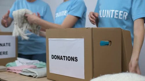 Social Center Volunteers Putting Clothes in Donation Boxes, Altruism Generosity
