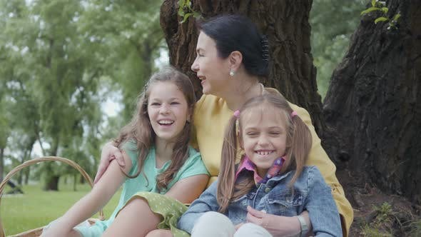 Thumbnail for Portrait Mature Cute Woman Kissing and Hugging Adorable Granddaughters Sitting on the Grass