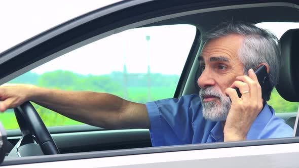 Thumbnail for Senior Man Sits in the Car and Calls with Smartphone - Closeup Shot From Side - Countryside