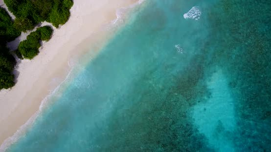 Wide angle fly over abstract shot of a white sandy paradise beach and aqua blue ocean background