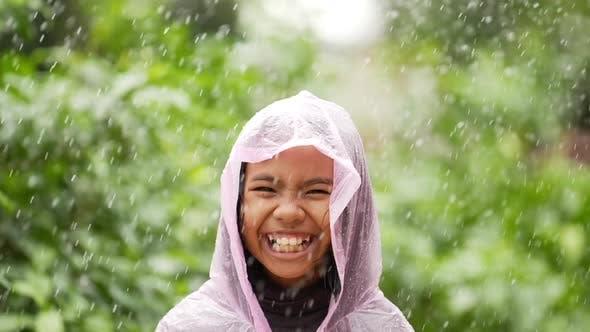 Happy girl wears raincoat