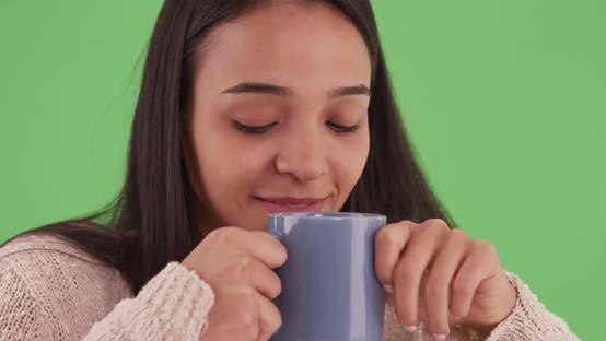Thumbnail for Hispanic Mädchen genießen den Geruch von Ihr heißes Getränk auf grünem Bildschirm