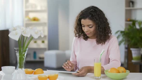 Thumbnail for Mixed Race Young Woman Reading Article on Tablet, Body Care and Nutrition