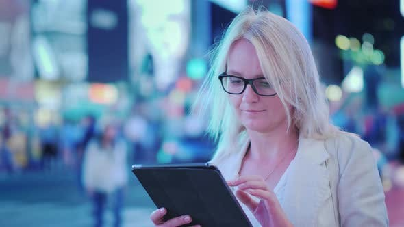 Cover Image for A Business Woman Uses a Tablet Behind It Is a Busy Street in Manhattan