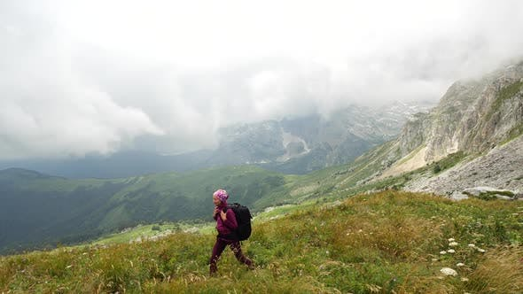Young Woman with Backpack Walks Towards the Summit. Slow Motion. Lady Is Hiking in Beautiful