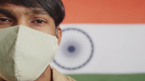 Man in Face Mask Posing against Indian Flag