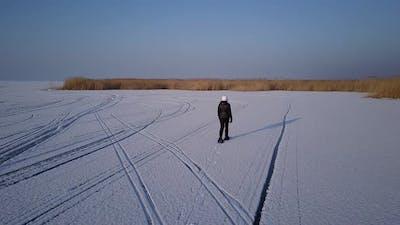 Drone Following Woman Walking on Icy Lake