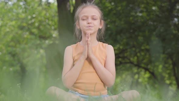 Thumbnail for Cute Little Ute Girl Sitting on the Grass Meditating. Child Practices Yoga. Summertime Leisure.