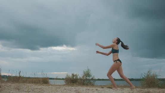 Slender Beach Volleyball Player Woman Is Serving Ball on Sand Court, Full Length Shot Against Cloudy