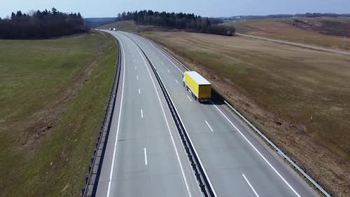 Aerial view of white semi truck with yellow cargo trailer, that moves on the highway.