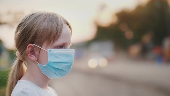 Thumbnail for A Child in a Protective Gauze Bandage Stands Near a Dusty Highway