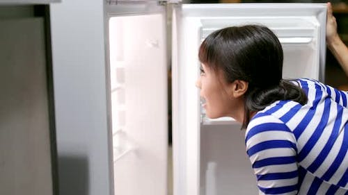 Woman feeling hungry and open refrigerator for food