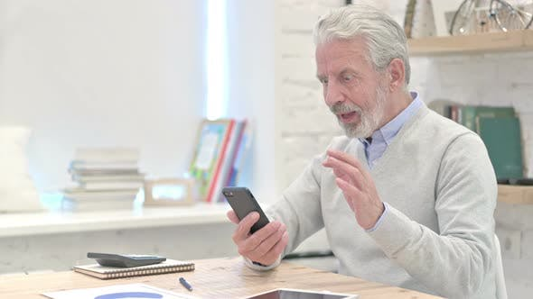 Thumbnail for Old Man Celebrating Success on Smartphone