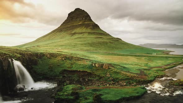 Cover Image for Waterfall Cascades And Mountain Fresh Green Grass At Sunset Light In Western Iceland