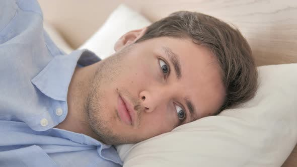 Thumbnail for Close Up of Thinking Young Man Lying on Side in Bed