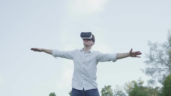 Thumbnail for Man Wearing Virtual Reality Headset Spread His Arms To the Side, Imitating the Flight of an Airplane