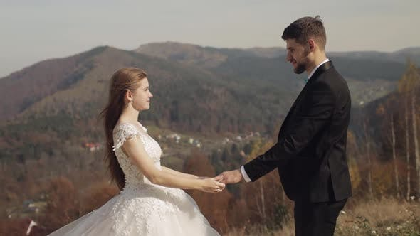 Cover Image for Newlyweds. Caucasian Groom with Bride on Mountain Slope. Wedding Couple. Happy