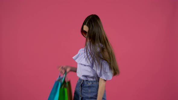 Thumbnail for Girl in Sunglasses Dancing with Packages in Their Hands. Pink Background