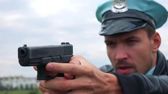 Thumbnail for A Young Police Officer Aims a Gun at Someone Off the Camera, Face Closeup