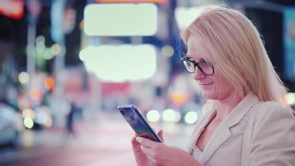 Cover Image for Woman in Glasses Uses a Smartphone on the Famous Times Square in New York