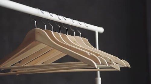Wooden Hanger on Dark Background. Number of Empty Hangers