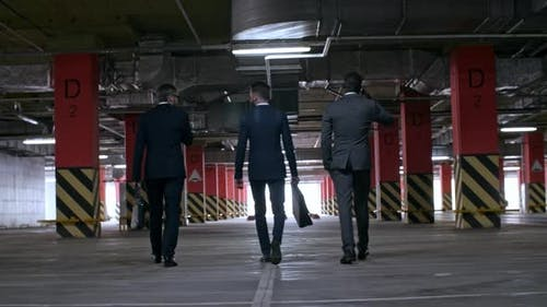 Geschäftsleute im Anzug zu Fuß in der unterirdischen Garage