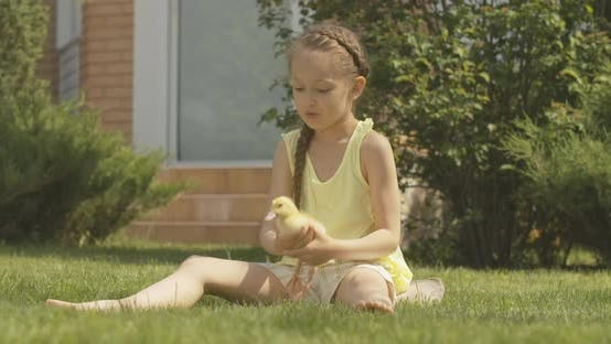 Wide Shot Portrait of Cheerful Caucasian Girl Playing with Duckling Outdoors and Leaving. Cute Child