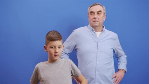 Grandfather with Grandson Doing Warmup on Blue Background