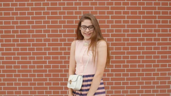Cover Image for Girl Student in Glasses Smiling and Showing Ok or Like Sign Against a Brick Wall Background